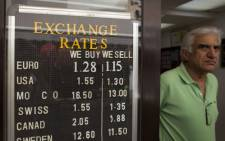 The owner of a currency exchange office stands next to his exchange rates board in Gibraltar, on 24 June 2016. Picture: Sergio Camacho/AFP.