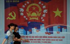 This picture taken on 21 April 2016 shows people walking past a propaganda poster featuring the upcoming legislative elections in downtown Hanoi. Picture: Hoang Dinh Nam/AFP.