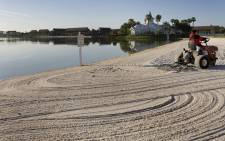 This file photo taken on 11 April 2008 shows a groundsman rake the beaches of Disney's Grand Floridian Resort & Spa at Disney World in Orlando, Florida. Picture: AFP.