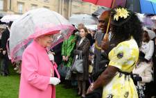 Britain's Queen Elizabeth II (L) talks to Pastor Kofi Banful and Jayne Banful in the garden of Buckingham Palace in London as up to 8,000 guests attend the first royal garden party of the year on May 10, 2016. Picture: AFP.