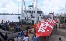 Workers load the tail of AirAsia flight QZ8501 onto a truck at Kumai sea port, in Central Kalimantan, on 7 February, 2015 before they transport it to Jakarta. Picture: AFP