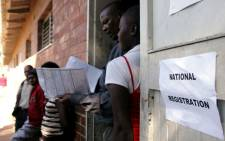 A voter registration official inspects identity particulars at Lotshe Primary School in Bulawayo, Zimbabwe on 7 May 2013 during the mobile voter registration exercise. Picture: AFP