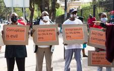 Members of the People's Movement hold placards outside the Bloemfontein Magistrates Court on 2 October 2020 where 7 suspects are appearing on corruption charged related to a multi-million rand Free State asbestos project. Picture: Xanderleigh Dookey/EWN