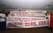 Chinese relatives of passengers from missing Malaysia Airlines flight MH370 display banners and the Chinese flag at a hotel in Subang Jaya on 30 March. Picture: AFP.