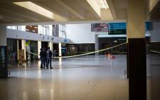 Police watch over a crime scene after at least two men dressed in black opened fire at Cape Town train station. Picture: Anthony Molyneaux/EWN.