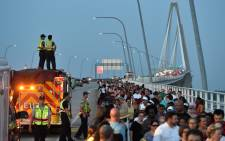 Firefighters greet people as thousands march on The Arthur Ravenel Jr Bridge in Charleston, South Carolina on 21 June, 2015. Picture: AFP.