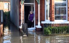 FILE: A woman looks out from a flooded property adjacent to the River Foss which burst its banks in York, northern England, on 27 December, 2015. Picture: AFP.