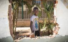 A young school boy looks through a vandalised window at the Tshinavhe Secondary School in Vuwani. Picture: Thomas Holder/EWN