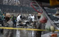 FILE: Afghan security personnel inspect a damaged car at the site of a suicide bomb attack near the international airport in Kabul on January 4, 2016. The bomber struck a street leading to Kabul's international airport, officials said. Picture: AFP.