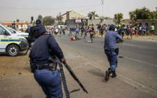 Residents run from members of the South African Police Service (SAPS) firing rubber bullets outside the SAPS offices in Eldorado Park, near Johannesburg, on 27 August 2020, during a protest by community members after a 16-year old boy was allegedly killed by police. Picture: AFP