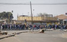 People stand near the looted and vandalised Lotsoho Mall in Katlehong township, east of Johannesburg, on 12 July 2021. Several shops are damaged and cars burnt in Johannesburg following a night of violence. Police are on the scene trying to control further protests. It is unclear if this is linked to sporadic protests following the incarceration of former president Jacob Zuma. Picture: Phill Magakoe/AFP