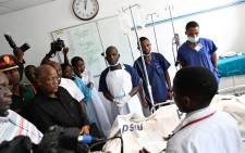 Tanzanian President John Pombe Magufuli talks to medical staff and victims of the Morogoro petrol tanker explosion, at the Muhimbili National Hospital in Dar es Salaam, on 11 August 2019.  Picture: AFP
