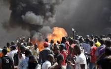 FILE: People stand in front of smoke rising from the Burkina Faso's Parliament, where demonstrators set fire to cars parked in a courtyard of the Parliament, on October 30, 2014. Picture: AFP.