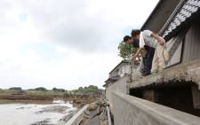 Local residents check a collapsed embankment following the floods from their residence in the city of Joso, Ibaraki prefecture on September 12, 2015. Picture: AFP.
