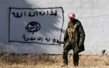 FILE: A Kurdish fighter walks by a wall bearing a drawing of the flag of the Islamic State (IS) group in the northern Iraqi town of Sinjar. Picture: AFP.