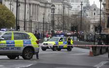 Armed police officers stand guard outside of the Houses of Parliament in central London on 22 March 2017 after a man drove his car through a crowd of people and stabbed a policeman. Picture: AFP.