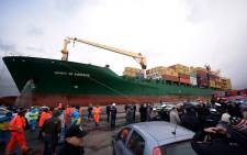 The Singapore-flagged cargo container ship Spirit of Piraeus, carrying 49 passengers evacuated from the ferry Norman Atlantic, arrives in the harbour of Bari on 29 December, 2014, as Italian advanced rescue personnel and police wait on the quay. Picture: AFP.