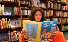 Lily Connor, 8, looks over a copy of Dr Seuss's never-before-published book 'What Pet Should I Get?' on the day it is released for sale at the Books and Books store on 28 July 2015 in Coral Gables, United States. Picture: AFP.