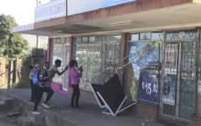 People take pictures of a damaged shop in Mbabane, Eswatini, on 29 June 2021. Picture: AFP.