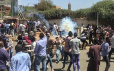 FILE: Sudanese protesters run for cover from tear gas canisters fired by police outside the military headquarters in the capital Khartoum on 6 April 2019. Protests have rocked the east African country since December, with angry crowds accusing Bashir's government of mismanaging the economy that has led to soaring food prices and regular shortages of fuel and foreign currency. Picture: AFP