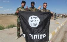 FILE: Iraqi Sunni and Shiite fighters pose for a photo with an Islamic State group flag in the Al-Alam town, northeast of the Iraqi city of Tikrit, on March 17, 2015 after recapturing the town from IS fighters earlier in the month. Picture: AFP.