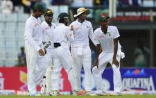 Bangladesh cricketers Shakib Al Hasan (2R) and Mustafizur Rahman (R) celebrate the dismissal of South Africa cricketer Simon Harmer during the first day of the first Test match between Bangladesh and South Africa at the Zahur Ahmed Chowdhury Stadium in Chittagong on 21 July, 2015. Picture:AFP.