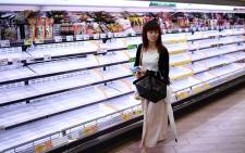 A woman walks past empty shelves in a store in Tokyo on 11 October 2019, as Typhoon Hagibis heads towards the city. Japan is bracing for a powerful typhoon barrelling towards Tokyo that has already forced the cancellation of two Rugby World Cup matches, disrupted the Suzuka Grand Prix and grounded flights. Picture: AFP