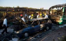 Israeli firemen and emergency services gather around the remains of a burnt-out bus and car after extinguishing the flames following an explosion in Jerusalem on 18 April, 2016. Picture: AFP.