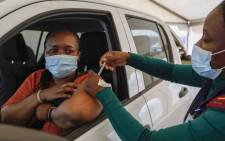 A woman receives a dose of the Johnson and Johnson COVID-19 vaccine from a healthcare worker at the Zwartkops Raceway in Centurion on 13 August 2021. Picture: Phill Magakoe/AFP