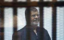File: Egypt's ousted Islamist president Mohamed Morsi stands behind the bars during his trial in Cairo on 16 June, 2015. Picture: AFP.