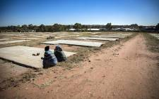Two people sit on a designated plot during a site visit by the Democratic Alliance (DA) of an abandoned low-cost housing project in Maryland's Extension, Germiston, Ekurhuleni. Picture: Sethembiso Zulu/EWN