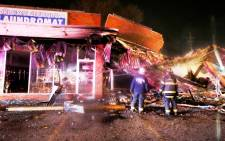 Firemen stand outside a burnt-out laundromat after protesters burned buildings in protest against the Grand Jury decision not to indict a police officer in the shooting death of Michael Brown, in Ferguson, Missouri, USA, 25 November 2014. Picture: EPA.