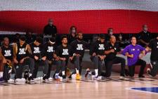 The Los Angeles Lakers and the LA Clippers kneel during the National Anthem prior to a game on 30 July 2020 at The Arena at ESPN Wide World Of Sports Complex in Orlando, Florida. Picture: AFP