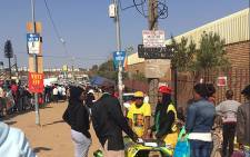 ANC members are pictured in Diepsloot on elections day, while voters queue on 3 August 2016. Picture: Clement Manyathela/EWN.