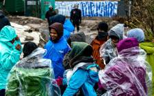FILE: Migrants from Eritrea protect themselves from rain in March 2016 in the so-called Jungle migrant camp in the French northern port city of Calais as agents dismantle shelters in the southern part of the camp. Picture: AFP
