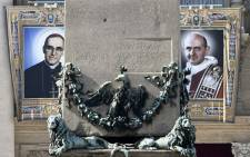 The tapestries of Roman Catholic Archbishop Oscar Romero (L) and Pope Paul VI hang from a balcony of the facade of St Peter's Basilica at the Vatican on 13 October 2018. Picture: AFP.