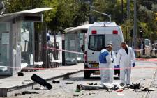 Israeli police inspect the scene where a Palestinian man drove a van into a crowd of police and civilians along the tracks of the Light Rail trolley system in East Jerusalem, 5 November 2014. Picture: EPA.