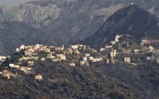 Burnt woodland surrounds a mountain town due to forest fires in the Ait Daoud area of northern Algeria, on 13 August 2021. Picture: AFP