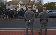 Two police officers stand guard as the press gathers outside a rabbi's home where a machete attack that took place earlier during the Jewish festival of Hanukkah, in Monsey, New York, on 29 December 2019. Picture: AFP.