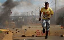 FILE: A boy runs from an approaching police nyala during violent service delivery protests during October. Picture: Sebabatso Mosamo/EWN.
