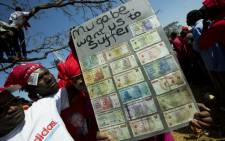 FILE: Anti-government supporters hold a sign with different Zimbabwean dollar bills ranging in value from 5 to 500 million, during an election rally in Harare on July 29, 2013. Picture: AFP.