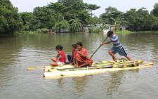 Indian residents use a makeshift raft to cross a flooded locality after the River Atreyee overflowed following heavy monsoon rains at Chakvrigu near Balurghat in South Dinajpur district of India's West Bengal state on 17 July 2019. Picture: AFP