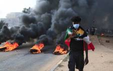 A Sudanese protester draped with the national flag flashes the victory sign next to burning tyres during a demonstration in the capital Khartoum, on 25 October 2021, to denounce overnight detentions by the army of members of Sudan's government. Picture: AFP