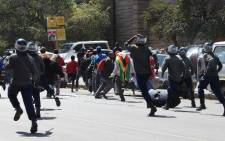 Zimbabwe police officers clash with demonstrators who had planned to hand in a petition at the finance ministry on 3 August 2016 in Harare, Zimbabwe. Picture: AFP.