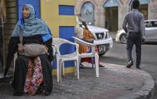 Noura Hassan (L), sits on a street corner alongside other traders, cradling a satchel filled with a variety of regional and international currencies, waiting on customers to come by for foreign-exchange (Forex) services in Djibouti's capital on 11 April 2021. Picture: Tony Karumba/AFP