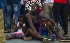 A Haitian migrant woman and her children remain in the main square of Tapachula, Chiapas state, Mexico on 14 September 2021. Picture: AFP