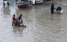 Pakistanis make their way on a flooded street after heavy rain in Karachi on August 31, 2017. The Pakistan Meteorological Department (PMD) has warned citizens against urban flooding in Karachi and other parts of lower Sindh due to heavy rain. Picture: AFP