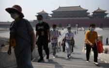 People wear face masks as a preventive measure against the COVID-19 coronavirus as they walk through the Forbidden City, the former palace of China's emperors, in Beijing on 1 May 2020. Picture: AFP