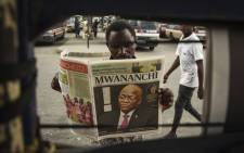 A man reads a newspaper with a headline announcing the death of Tanzania's President John Magufuli in Dar es Salaam, on 18 March 2021. Picture: AFP.