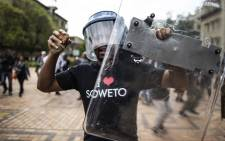 FILE: Wits student leader Mcebo Dlamini dances with a helmet and shield belonging to the university's private security during clashes with the police on campus on 4 October 2016 in Johannesburg. Picture: AFP.